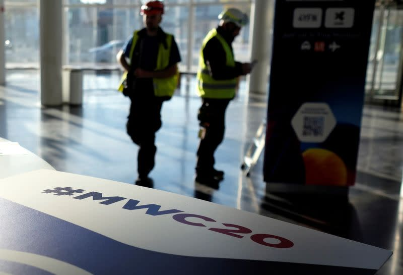 Employees work next to a banner with information of MWC20 in Barcelona