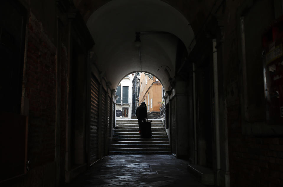 A man walks in an empty St. Mark's square arcade in Venice, Italy, Saturday, Jan. 30, 2021. Gondolas and other vessels are moored instead of preparing for Carnival's popular boat parade in the lagoon. Alleys are eerily empty. Venetians and the city's few visitors stroll must be masked in public places, indoors and out, under a nationwide mandate. (AP Photo/Antonio Calanni)