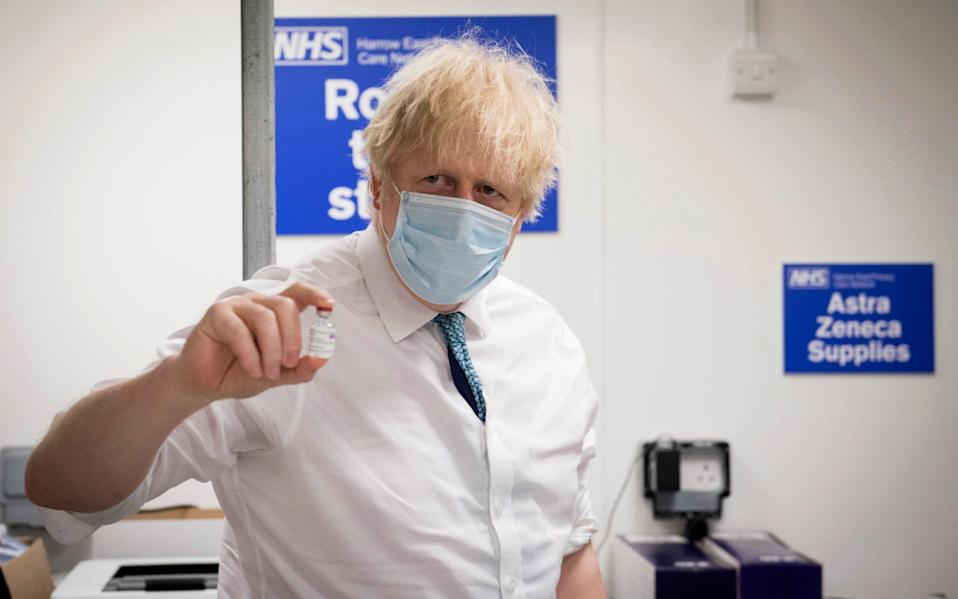 Boris Johnson holds a vial of the Oxford AstraZeneca COVID-19 vaccine - Pool PA