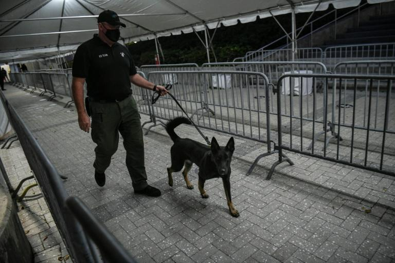 A K-9 handler walks with a specially trained dog that detects coronavirus in people at the American Airlines Arena prior to the NBA basketball match between Miami Heat and the LA Clippers in Miami, on January 28, 2021