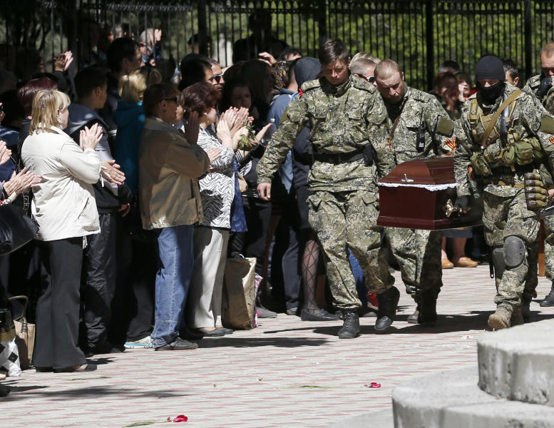 Pro-Russian gunmen carry the coffin of a person killed during clashes last week between Ukrainian and pre-Russian forces, during a commemoration service in the center of Slovyansk, eastern Ukraine, Wednesday, May 7, 2014. The U.S. and European nations have increased diplomatic efforts ahead of Ukraine's May 25 presidential election, as a pro-Russian insurgency continues to rock the country's eastern regions. (AP Photo/Darko Vojinovic)