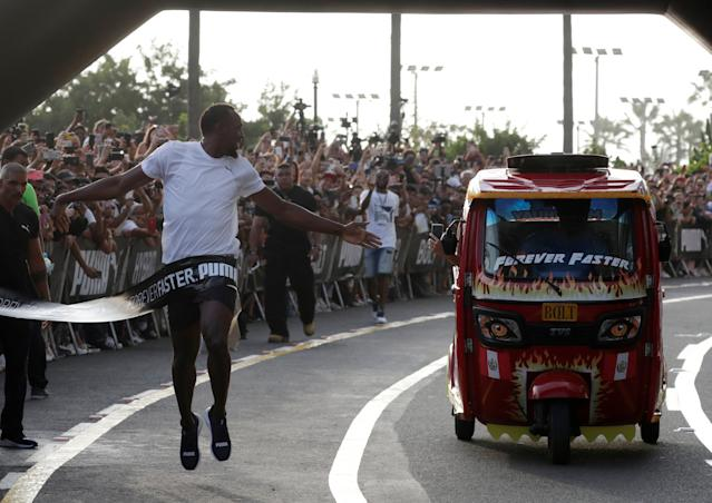 Usain Bolt runs against a moto-taxi as part of a sponsored event in Lima, Peru - April 2, 2019 REUTERS/Henry Romero TPX IMAGES OF THE DAY