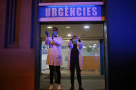 FILE - In this March 16, 2020 file photo, health workers react as people applaud from their houses in support of the medical staff that are working in COVID-19 outbreak in Barcelona, Spain. Spain is restoring border controls and severely restricting who can enter the country. (AP Photo/Joan Mateu, File)