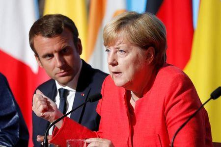 FILE PHOTO: French President Emmanuel Macron (L) and German Chancellor Angela Merkel attend a news conference following talks on European Union integration, defence and migration at the Elysee Palace in Paris, France August 28, 2017. REUTERS/Charles Platiau