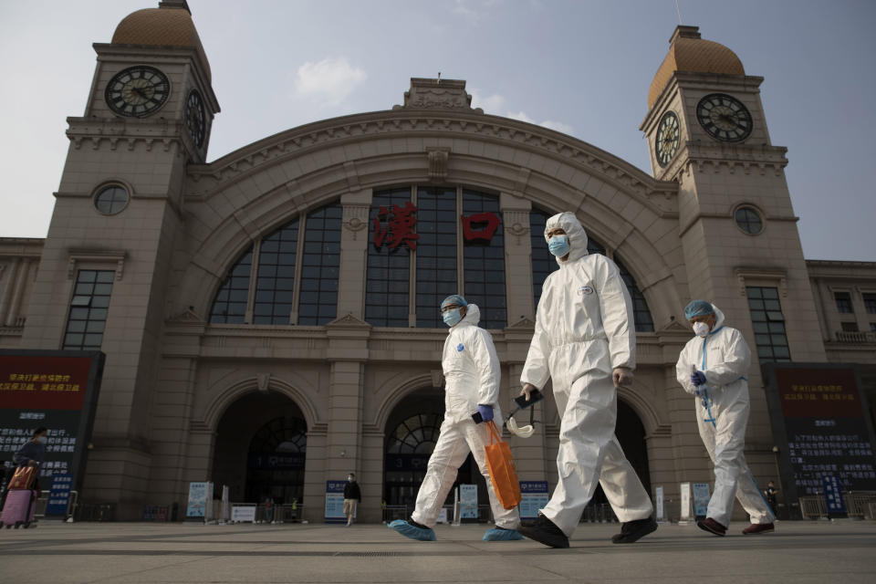 FILE - April 7, 2020, file photo, workers in protective overalls walk past the Hankou railway station on the eve of its resuming outbound traffic in Wuhan in central China's Hubei province. One year after Wuhan's lockdown to curb the coronavirus, the Chinese city has long since sprung back to life. (AP Photo/Ng Han Guan, File)