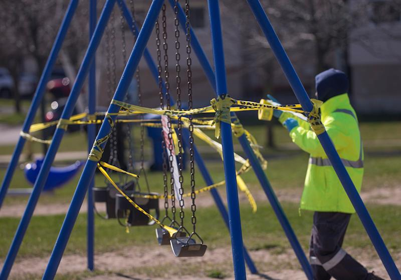 A City of Toronto employee reinstalls caution tape that was torn off a swing set on April 27, 2020. (Photo: Rick Madonik/Getty Images)