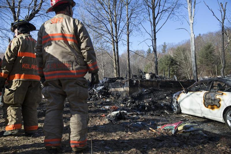 South Deerfield firemen stand at the scene following a deadly house fire, Saturday, March 4, 2017, in Warwick, Mass. A mother and four children were killed when flames swept through their rural Massachusetts home early Saturday, fire officials said. Two other family members escaped the fire, which broke in the single-family house. (Kieran Kesner /The Boston Globe via AP, Pool)