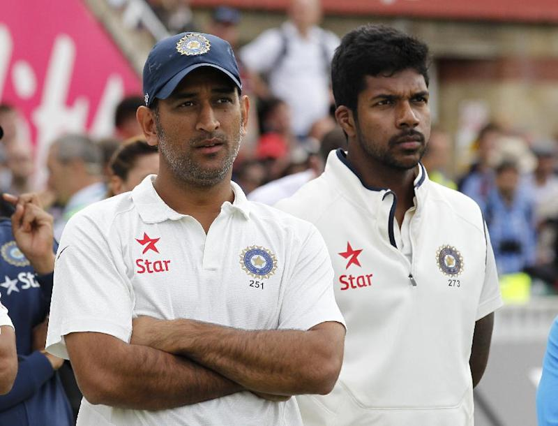 India's Mahendra Singh Dhoni (L) and Varun Aaron watch the presentation of the trophy to England after the fifth Test at The Oval in London on August 17, 2014