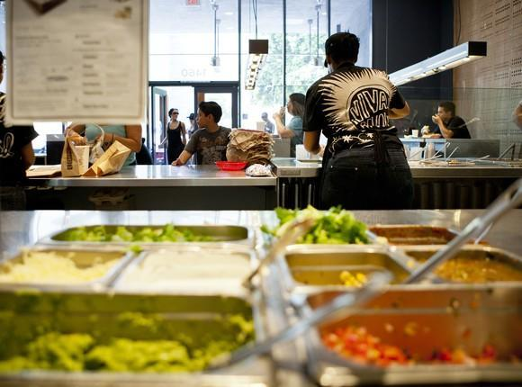Inside a Chipotle Mexican Grill restaurant with the food line and workers.
