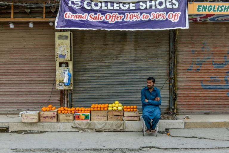 A man sells oranges in front of shuttered shops at a market in Rawalpindi, Pakistan. Most economic activity in south Asia has ground to a halt (AFP Photo/Farooq NAEEM)