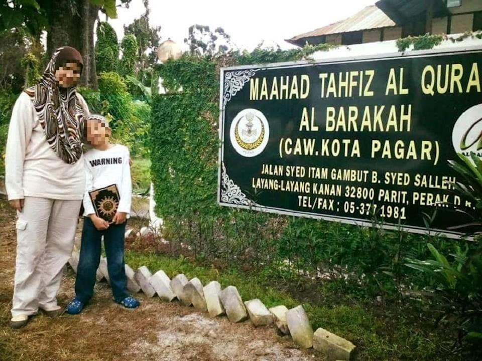An undated photo of the victim and his mother in front of Maahad Tahfiz al Barakah — the tahfiz school in Manjoi formerly owned by celebrity preacher Datuk Kazim Elias.