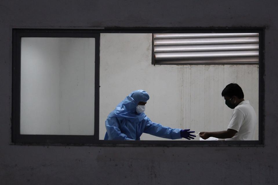 A healthcare worker wearing personal protective equipment (PPE) checks documents of a man during a medical check-up in Mumbai, India on July 27, 2020. India has become the third country after the United States and Brazil, to cross 01 million COVID-19 cases. (Photo by Himanshu Bhatt/NurPhoto via Getty Images)