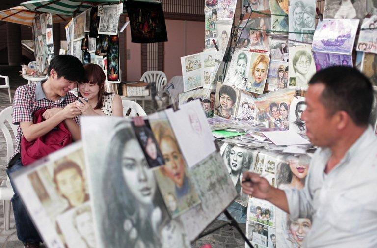 Chinese tourists look at a mobile phone while being drawn by a street artist in Hong Kong on May 9, 2013