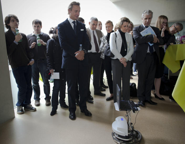Swiss billionaire philanthropist Ernesto Bertarelli, fourth from left, follows a robot controlled by Mark-Andre Duc, a partially tetraplegic patient at Switzerland's Federal Institute of Technology in Lausanne, Switzerland, Tuesday, April 24, 2012. From the hospital 100 kilometers (62 miles) away, Duc imagined lifting his fingers to direct a robot. Swiss scientists demonstrated with this test how a partially paralyzed person can control a robot using brain signals alone. (AP Photo/Anja Niedringhaus)