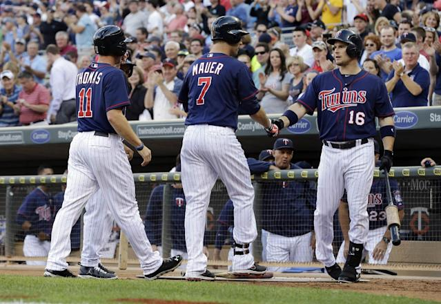 Minnesota Twins' Joe Mauer, center, and Clete Thomas, left, are welcomed by Josh Willingham, right, after Mauer's two-run home run off Chicago White Sox pitcher Dylan Axelrod in the first inning of a baseball game, Tuesday, June 18, 2013 in Minneapolis. (AP Photo/Jim Mone)