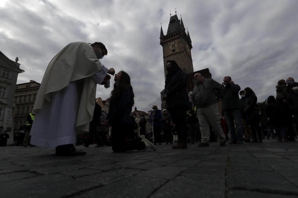 Dozens of worshippers attend a mass celebrated at Old Town Square in Prague, Czech Republic, Sunday, Oct. 18, 2020. As Czech Republic battles new spike of coronavirus infections newly adopted COVID-19 restrictive measures limit indoor gatherings to six people or less. (AP Photo/Petr David Josek)