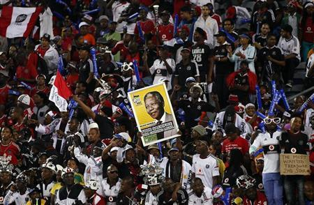 Fans of South Africa's Orlando Pirates hold a placard of anti-apartheid leader and former president Nelson Mandela during the first leg of their African Champions League final soccer match against Egypt's Al Ahli at Orlando Stadium in Soweto November 2, 2013. REUTERS/Siphiwe Sibeko