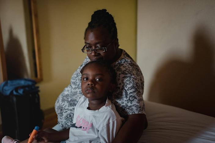 Latrish Oseko, 39, sits with her daughter, at a hotel in Newark, Del., on Thursday, Aug. 6, 2020, where they have been staying. (Hannah Yoon/The New York Times)