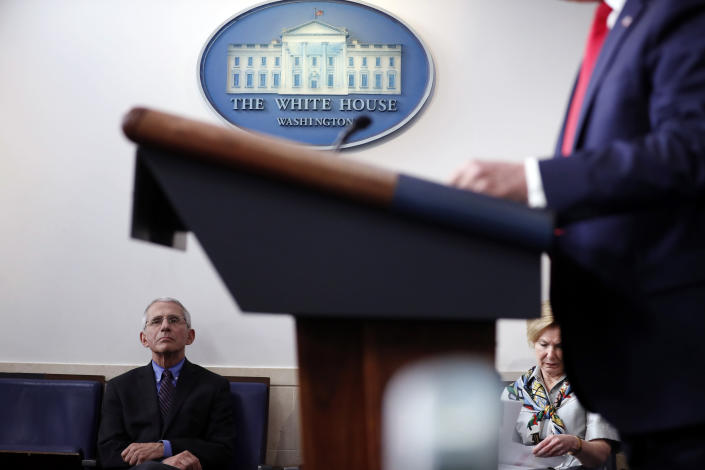 FILE - In this April 9, 2020, file photo, Dr. Anthony Fauci, director of the National Institute of Allergy and Infectious Diseases, and Dr. Deborah Birx, White House coronavirus response coordinator, listens as President Donald Trump speaks about the coronavirus in the James Brady Press Briefing Room of the White House, in Washington. After decades of renown in American medicine, Dr. Fauci has become an unlikely celebrity in his role as director of the National Institute of Allergy and Infectious Diseases, where he has led the medical response to COVID-19 and tried to inform an anxious nation. (AP Photo/Andrew Harnik, File)
