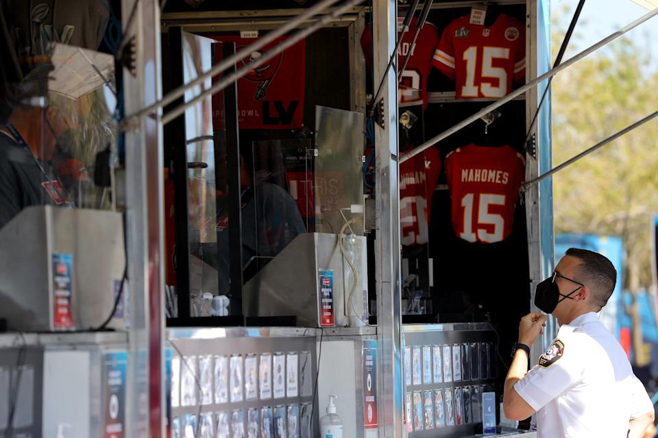 A first responder looks at merchandise from a vendor before Super Bowl LV between the Tampa Bay Buccaneers and the Kansas City Chiefs at Raymond James Stadium on February 07, 2021 in Tampa, Florida. (Photo by Kevin C. Cox/Getty Images)