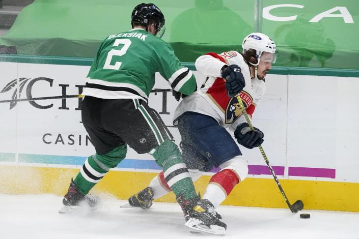 Dallas Stars defenseman Jamie Oleksiak (2) pressures Florida Panthers left wing Ryan Lomberg (94) as he handles the puck in the first period of an NHL hockey game in Dallas, Saturday, April 10, 2021. (AP Photo/Tony Gutierrez)