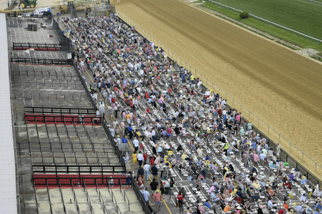 FILE - In this May 18, 2019, file photo, fans sit in front of a condemed section of grandstand ahead of the the 144th Preakness Stakes horse race at Pimlico race course, in Baltimore. The Preakness will remain at Pimlico Race Course into the foreseeable future, thanks to the passing of a bill to redevelop Maryland's race tracks with $375 million in bonds. (AP Photo/Nick Wass, File)
