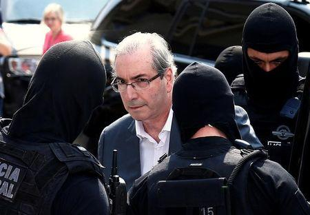 FILE PHOTO: Former speaker of Brazil's Lower House of Congress, Eduardo Cunha (C), is escorted by federal police officers as he leaves the Institute of Forensic Science in Curitiba, Brazil, October 20, 2016. REUTERS/Rodolfo Buhrer/File photo