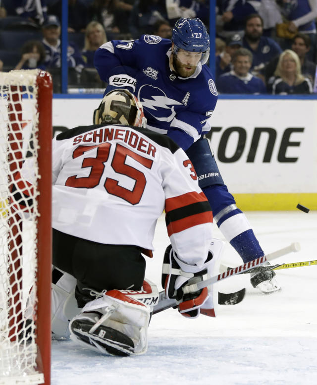 New Jersey Devils goaltender Cory Schneider (35) stops a shot by Tampa Bay Lightning defenseman Victor Hedman (77) during the second period of Game 5 of an NHL first-round hockey playoff series Saturday, April 21, 2018, in Tampa, Fla. (AP Photo/Chris O'Meara)