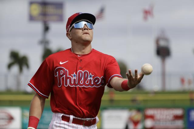 Philadelphia Phillies' Simon Muzziotti tosses a ball to a fan during the third inning of a spring training baseball game against the Toronto Blue Jays Tuesday, Feb. 25, 2020, in Clearwater, Fla. (AP Photo/Frank Franklin II)