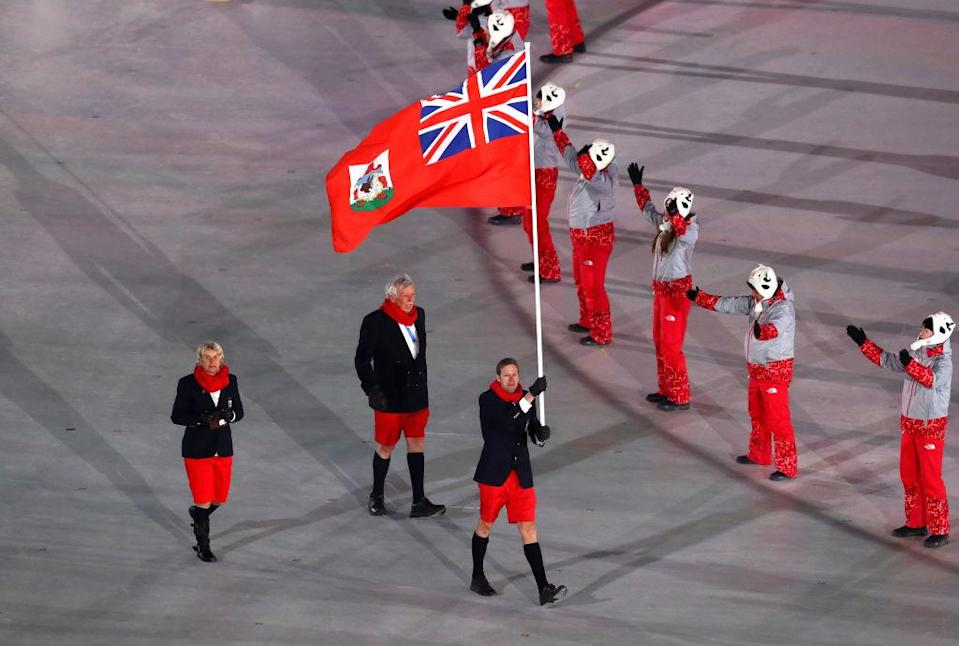<p>Flag bearer Tucker Murphy of Bermuda and teammates wear navy blazers, red shorts, matching scarves, and knee-high socks when entering the stadium during the opening ceremony of the 2018 PyeongChang Games. (Photo: Dean Mouhtaropoulos/Getty Images) </p>