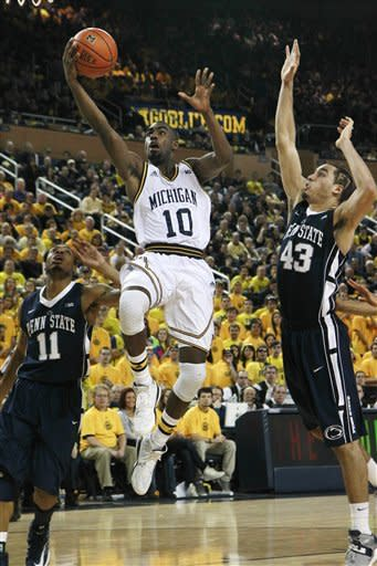 Michigan guard Tim Hardaway Jr. (10) goes between Penn State guard Jermaine Marshall (11) and forward Ross Travis (43) for a layup during the second half of an NCAA college basketball game at Crisler Center in Ann Arbor, Mich., Sunday, Feb. 17, 2013. (AP Photo/Carlos Osorio)