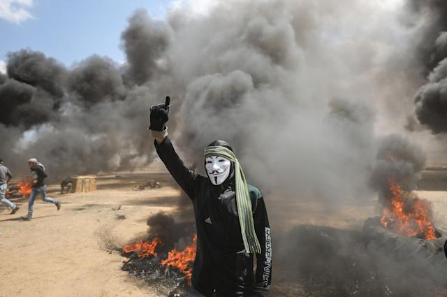 <p>Palestinians set tires on fire in response to Israel's intervention during a protest to mark the 70th anniversary of Nakba, also known as Day of the Catastrophe in 1948, and against the relocation of the U.S. Embassy from Tel Aviv to Jerusalem, near the Gaza-Israel border in Khan Younis on May 14, 2018. (Photo: Mustafa Hassona/Anadolu Agency/Getty Images) </p>
