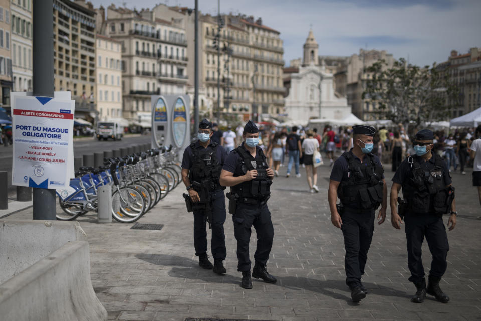 French riot police officers watch residents wearing face masks in Marseille, southern France, Tuesday, Aug.18, 2020. The French government is sending riot police to the Marseille region to help enforce mask requirements, as more and more French towns and neighborhoods are imposing mask rules starting Monday to slow rising infections. (AP Photo/Daniel Cole)