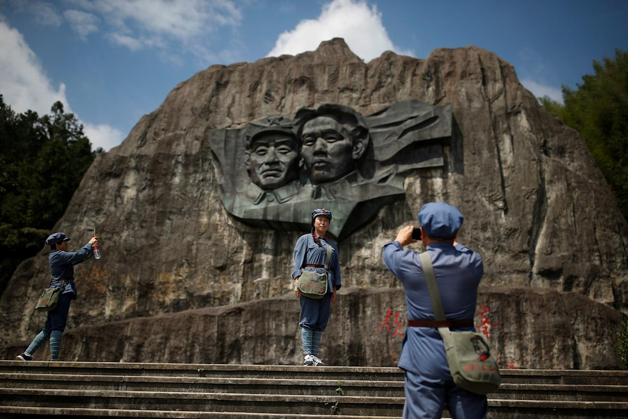"Participants dressed in replica red army uniforms take pictures at a base relief showing former Chinese communist leaders Mao Zedong and Zhu De at a historic site of the Long March in the mountains outside Jinggangshan, Jiangxi province, China, September 14, 2017. REUTERS/Thomas Peter  SEARCH ""LONGMARCH PETER"" FOR THIS STORY. SEARCH ""WIDER IMAGE"" FOR ALL STORIES. TPX IMAGES OF THE DAY."