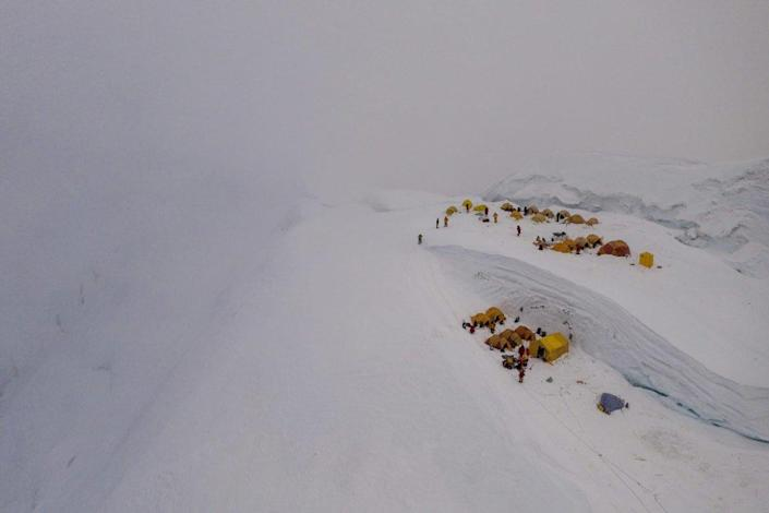 """<div class=""""inline-image__caption""""> <p>Just before a storm, tents from several expeditions huddle against the snowy slope in this drone shot of the North Col camp at about 23,000 feet. But the hurricane-force winds that followed proved too strong, blasting down every tent. At least one was carried hundreds of feet into the air. </p> </div> <div class=""""inline-image__credit""""> National Geographic/Renan Ozturk </div>"""