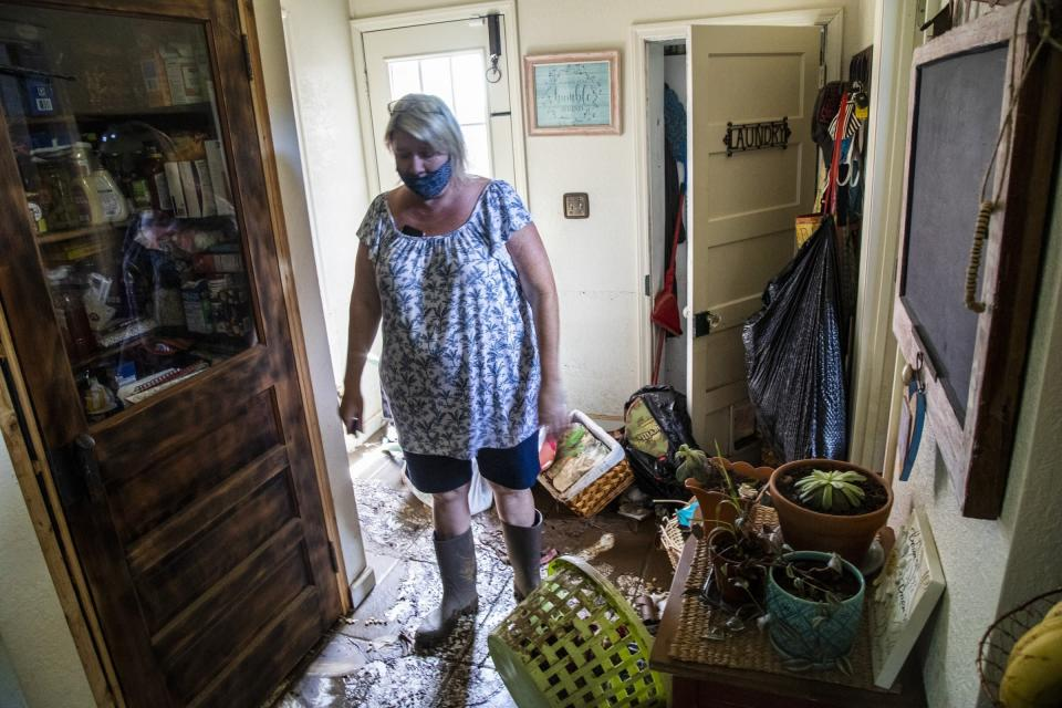 Donella Pressley looks over the flood damage to her home Thursday, Aug. 19, 2021 in Bethel , N.C., after remnants from Tropical Storm Fred caused flooding in parts of Western North Carolina Tuesday. (Travis Long/The News & Observer via AP)
