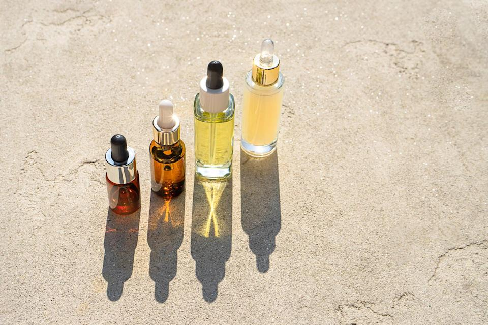Glass bottles of beauty serum or oil or lotion products with shadows on concrete background on sunlight. Essential natural oil for face and body. Organic minimal layout. Creative concept.