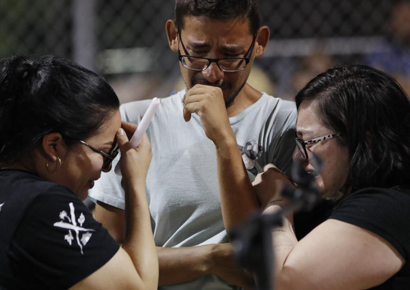 Employees of Walmart cry as they attend a vigil for victims of Saturday's mass shooting who were killed at the store inside a shopping complex Sunday, Aug. 4, 2019, in El Paso, Texas. (AP Photo/John Locher)