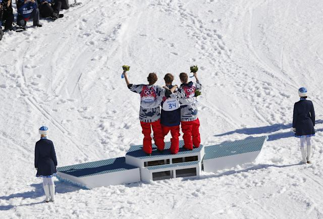 Men's ski slopestyle gold medal winner Joss Christensen of the United States, center, celebrates on the podium with his teammates Gus Kenworthy, right, silver, and Nicholas Goepper, bronze, left, during a flower ceremony at the Rosa Khutor Extreme Park, at the 2014 Winter Olympics, Thursday, Feb. 13, 2014, in Krasnaya Polyana, Russia. (AP Photo/Sergei Grits)