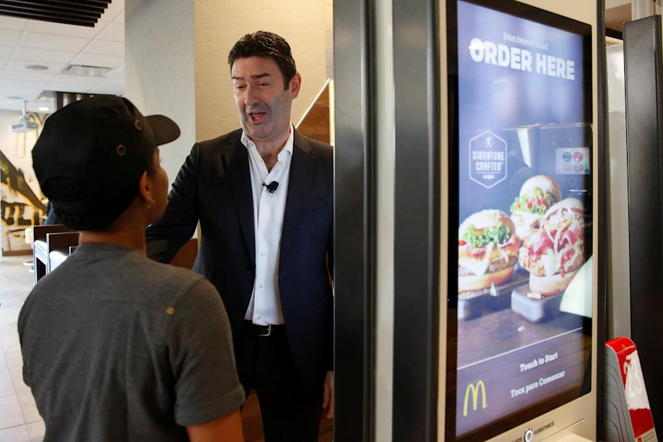McDonald's CEO Steve Easterbrook speaks with an employee by a self-service ordering kiosk before a press conference in New York November 17, 2016.  REUTERS/Shannon Stapleton