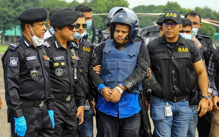 Rapid Action Battalion personnel escort Mohammad Shahed, centre - who is accused of distributing fake coronavirus certificates - following his arrest in Dhaka - AFP