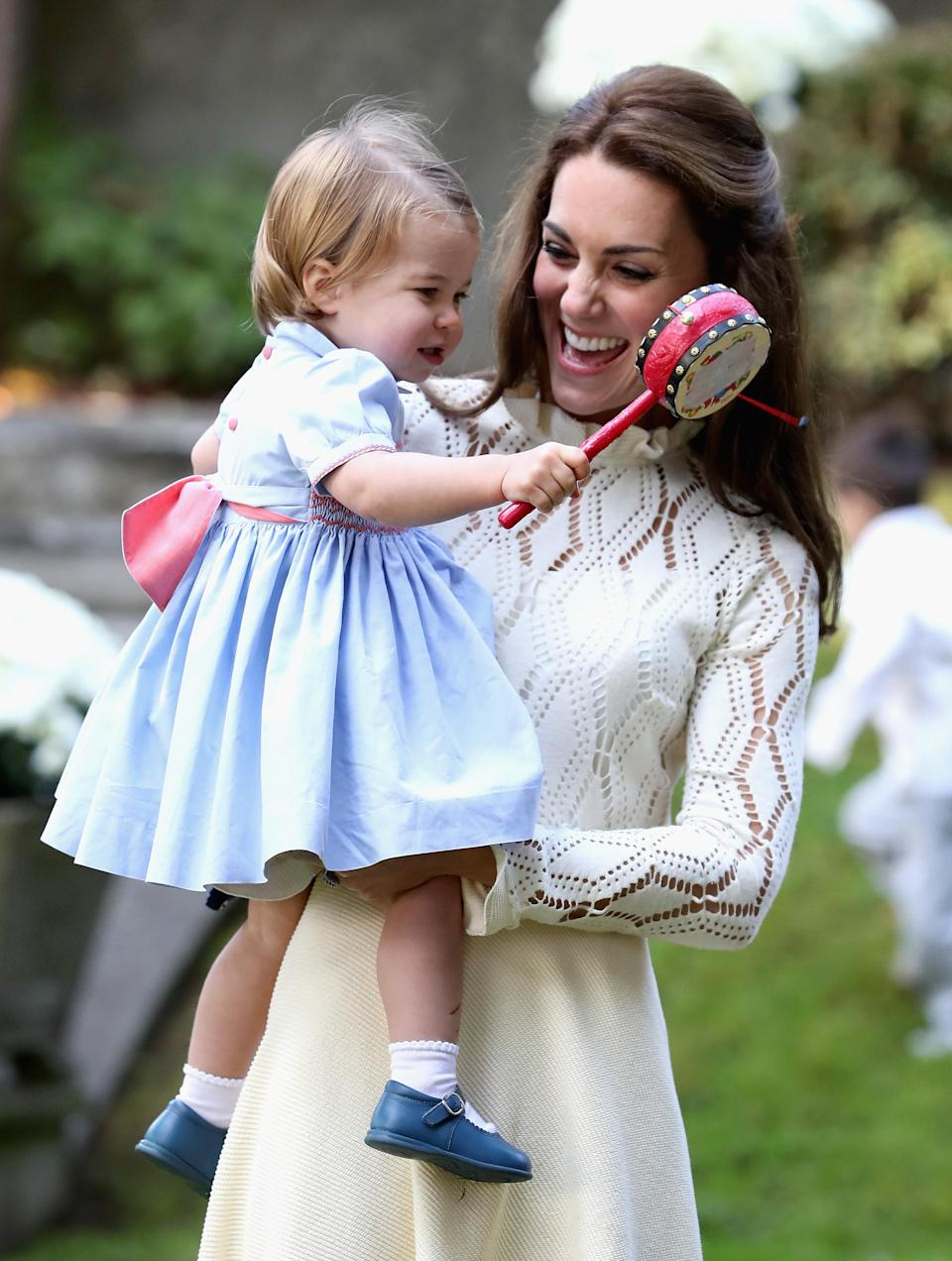 <p>The Duchess and little Charlotte looked adorable enjoying some light-hearted fun at a children's party.</p>