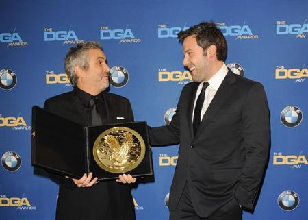 """Ben Affleck smiles as he presents Mexican director Alfonso Cuaron with the Feature Film award for """"Gravity"""" during the 66th annual Directors Guild of America Awards in Beverly Hills"""