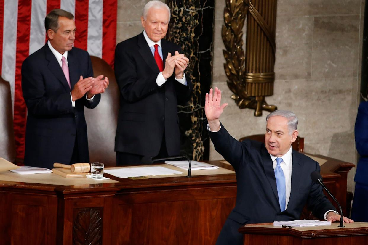 Israeli Prime Minister Benjamin Netanyahu waves as he steps to the lectern prior to speaking before a joint meeting of Congress on Capitol Hill in Washington on March 3, 2015. House Speaker John Boehner of Ohio, left, and Sen. Orrin Hatch (R-Utah) applaud.