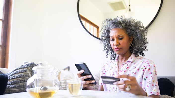 A black woman makes a purchase on her smartphone.