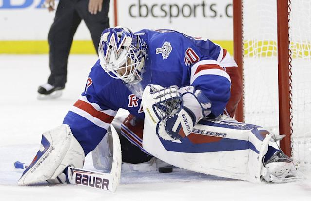 A shot on goal by the Los Angeles Kings slips through the legs of New York Rangers goalie Henrik Lundqvist (30) to rest near the goal line before being swatted out by Rangers center Derek Stepan in the third period during Game 4 of the NHL hockey Stanley Cup Final, Wednesday, June 11, 2014, in New York. The Rangers won 2-1. (AP Photo/Seth Wenig)