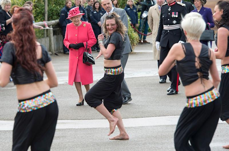 Queen Elizabeth II watches dancers perform as she visits Chester Zoo as part of her tour of the North West on May 17, 2012 in Chester, England