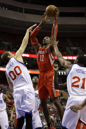 Houston Rockets' Dwight Howard (12) goes up for a shot against Philadelphia 76ers' Spencer Hawes (00) and Thaddeus Young (21) during the first half of an NBA basketball game, Wednesday, Nov. 13, 2013, in Philadelphia. (AP Photo/Matt Slocum)