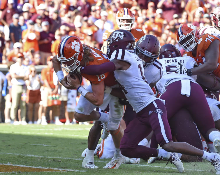 Clemson's Trevor Lawrence, left, scores a touchdown while being defended by Texas A&M's Keldrick Carper during the first half of an NCAA college football game Saturday, Sept. 7, 2019, in Clemson, S.C. (AP Photo/Richard Shiro)