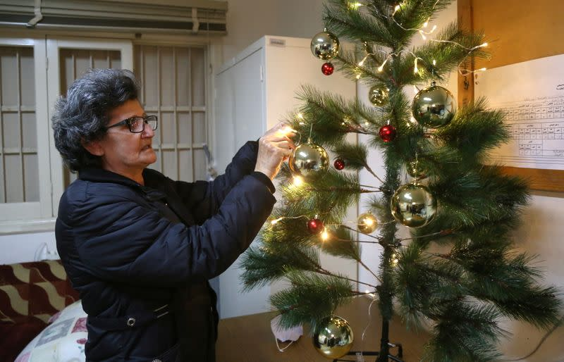 Georgette Suleiman, 63, who looks after a Beirut school damaged by the Beirut port blast decorates a Christmas tree in Beirut